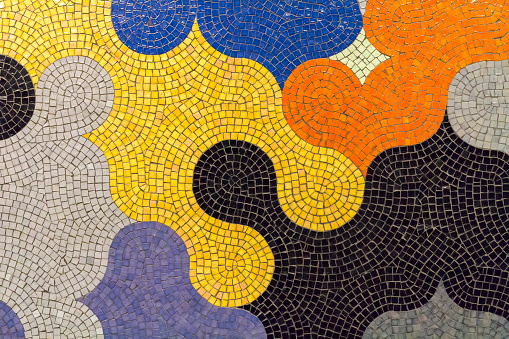 Modern ceramic mosaic in puzzle shapes with many colors in a wall in Rome, Italy. Abstract colorful background in geometrical shapes.