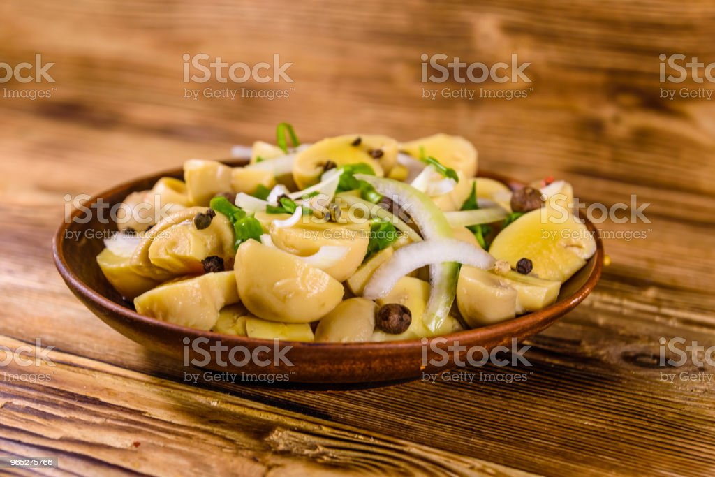 Ceramic plate with canned mushrooms on wooden table royalty-free stock photo