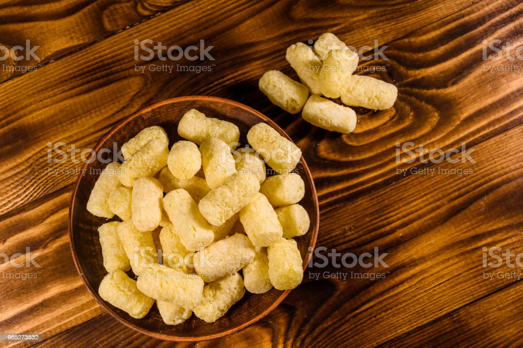 Ceramic plate with corn sticks on wooden table. Top view royalty-free stock photo