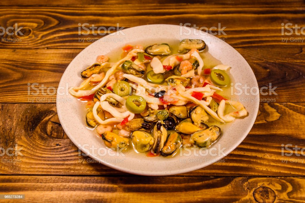 Ceramic plate with different sea food and olives on wooden table royalty-free stock photo