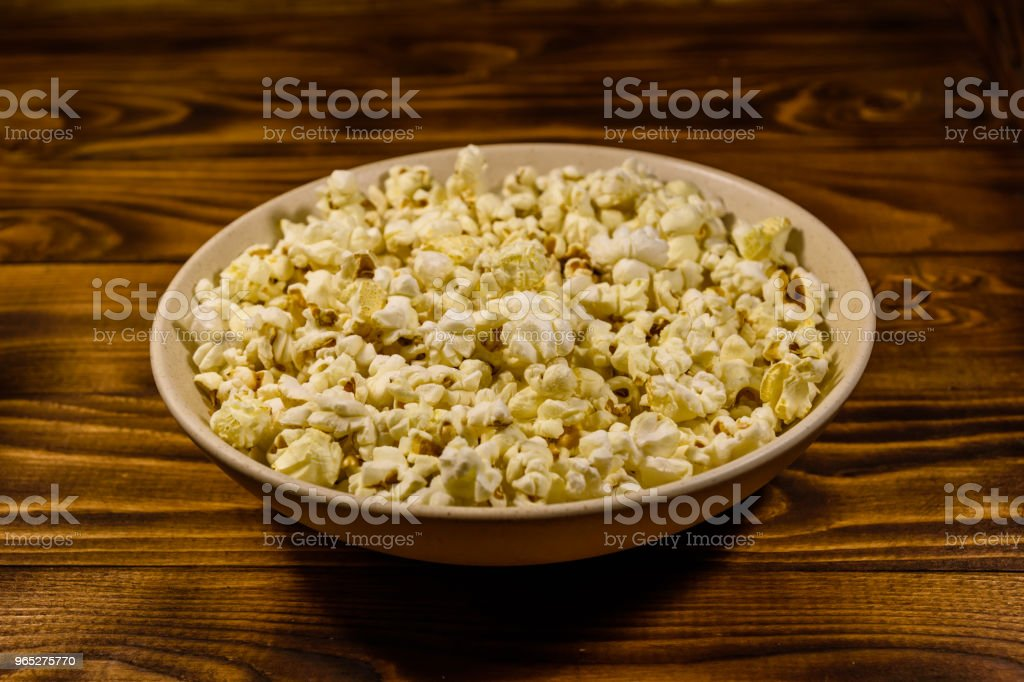 Ceramic plate with popcorn on wooden table zbiór zdjęć royalty-free