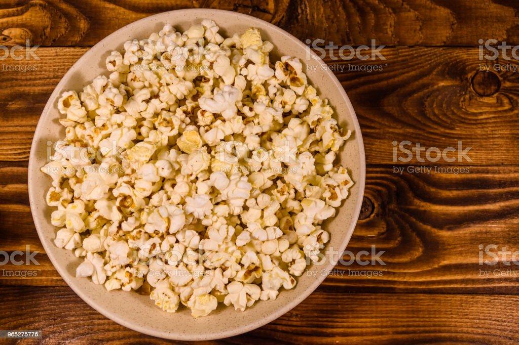 Ceramic plate with popcorn on wooden table. Top view zbiór zdjęć royalty-free