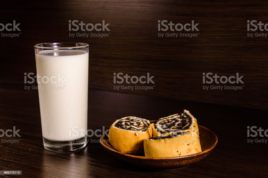 Ceramic plate with poppy seed buns and a glass of milk on dark wooden table royalty-free stock photo