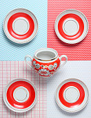 Ceramic saucers and teapots on a creative background, top view