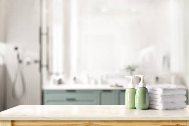 Ceramic shampoo, soap bottle and towels on counter over bathroom background. table top and copy space Ceramic shampoo, soap bottle and towels on counter over bathroom background. table top and copy space bathroom stock pictures, royalty-free photos & images