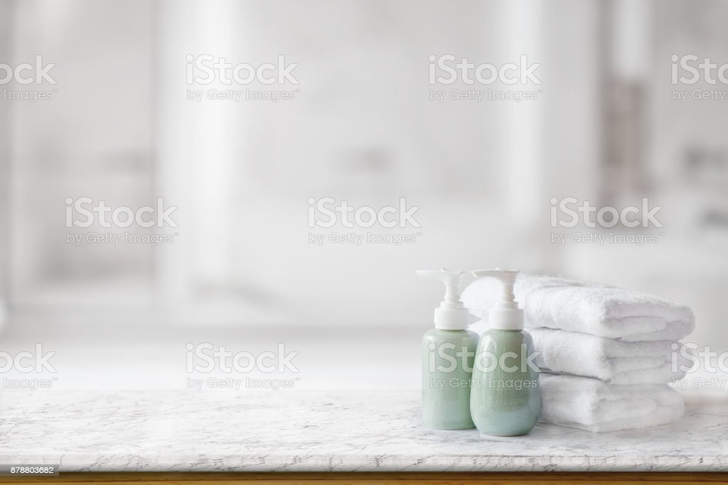 Ceramic soap green bottles and white cotton towels on a marble counter table inside a bright bathroom background. stock photo