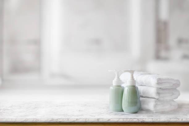 ceramic soap green bottles and white cotton towels on a marble counter table inside a bright bathroom background. - prodotto per l'igiene personale foto e immagini stock