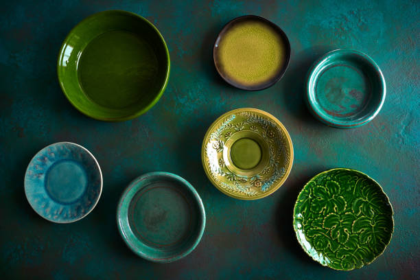 Ceramic tableware dishes plates on grungy Ceramic tableware dishes plates on grunge green background pottery stock pictures, royalty-free photos & images