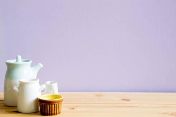 keramik geschirr auf holztisch mit hellen lila hintergrund - küche deko lila stock-fotos und bilder