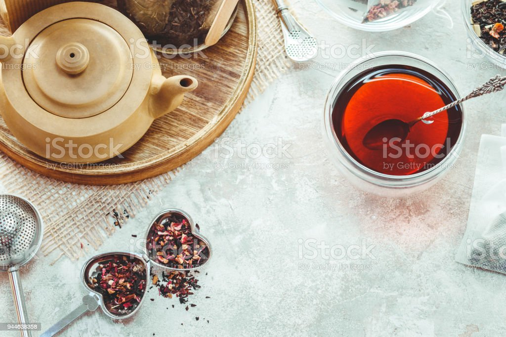 Ceramic tea pot, metal tea infuser and cup of black tea. Composition with tea accessories on a white background stock photo