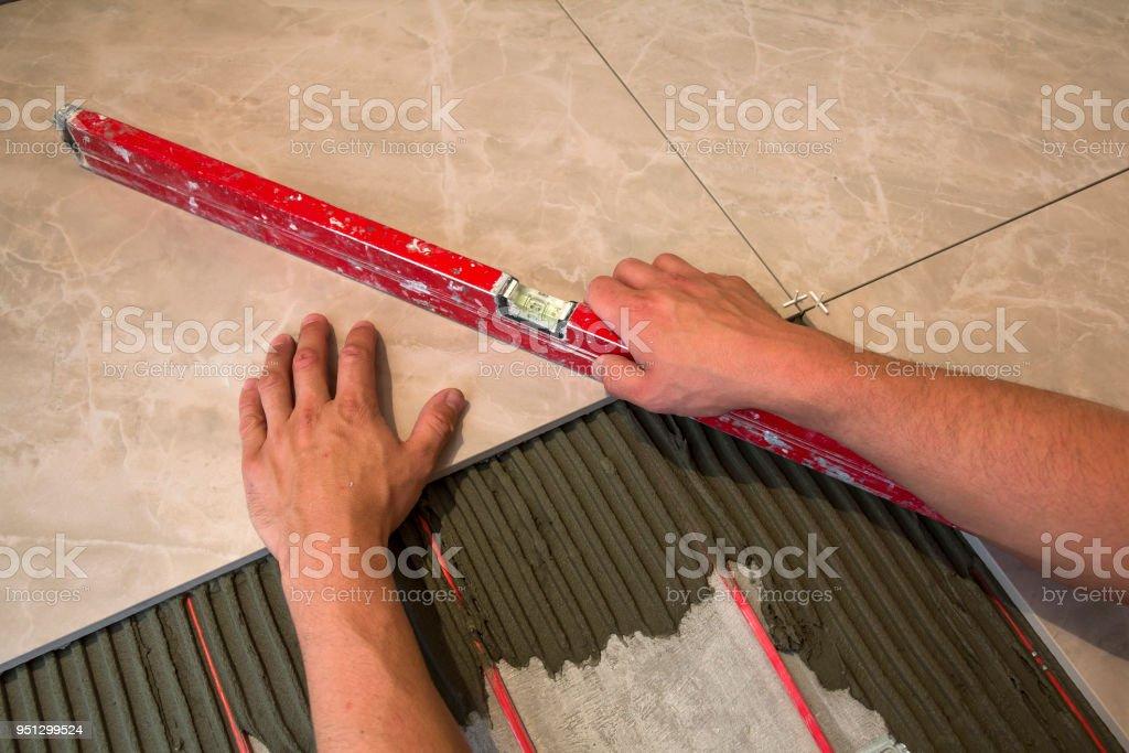 Ceramic Tiles And Tools For Tiler Worker Hand Installing Floor Tiles