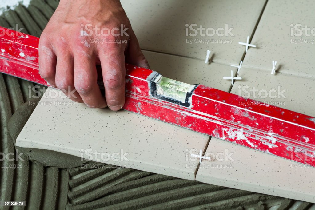 Ceramic Tiles And Tools For Tiler Worker Hand Installing Floor Tiles