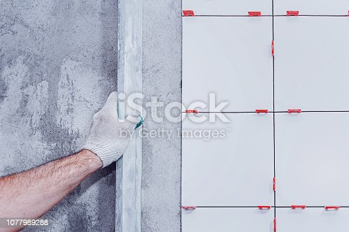 istock Ceramic tiles. The master lays ceramic tiles on the wall and draws them out using a special level. 1077989288