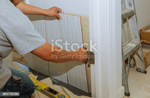 1138442636 istock photo Ceramic Tiles. Tiler placing ceramic wall tile in position over adhesive 955703260