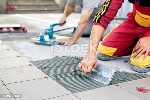 istock Ceramic Tiles. Tiler placing ceramic wall tile in position over adhesive, with handy man in background cutting ceramic tile. 1058762004