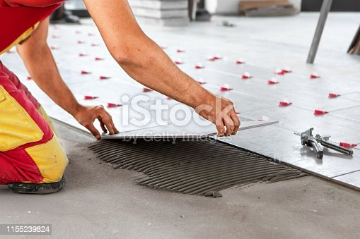 istock Ceramic Tiles. Tiler placing ceramic wall tile in position over adhesive with lash tile leveling system - Image 1155239824
