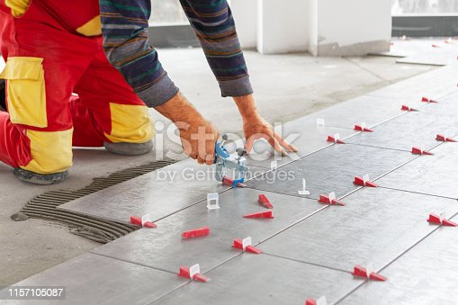 istock Ceramic Tiles. Tiler placing ceramic wall tile in position over adhesive with lash tile leveling system 1157105087