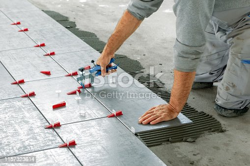 istock Ceramic Tiles. Tiler placing ceramic wall tile in position over adhesive with lash tile leveling system 1157323614