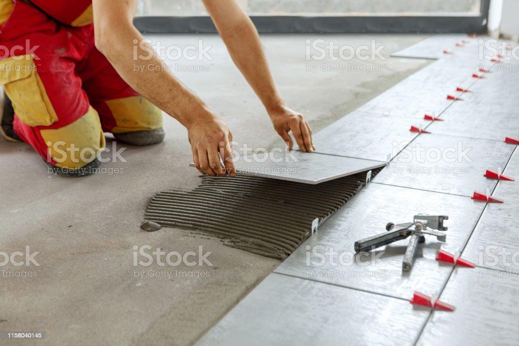 Telhas cerâmicas. Tiler que coloc a telha cerâmica da parede na posição sobre o adesivo com sistema nivelando da telha do chicote - Foto de stock de Aprimoramento royalty-free