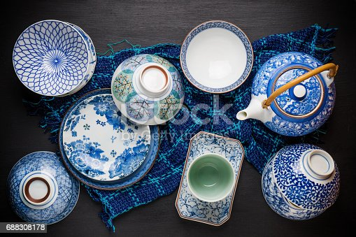 Ceramic utensils, bowl plate and teapot on table. Top view