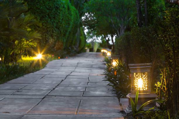 ceramic ware lamp street in the garden walkway at twilight - zona pedonale struttura creata dall'uomo foto e immagini stock