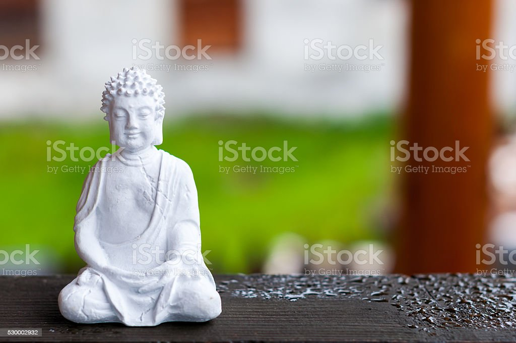 Ceramic Zen Buddha Statue Meditating with Blurred Texture Background. Yoga stock photo