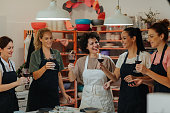 Group of women on ceramics workshop with their female instructor cheering with red wine.