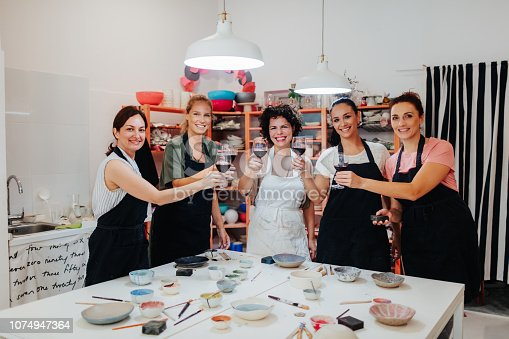 Group of women on ceramics workshop with their female instructor toasting with red wine.