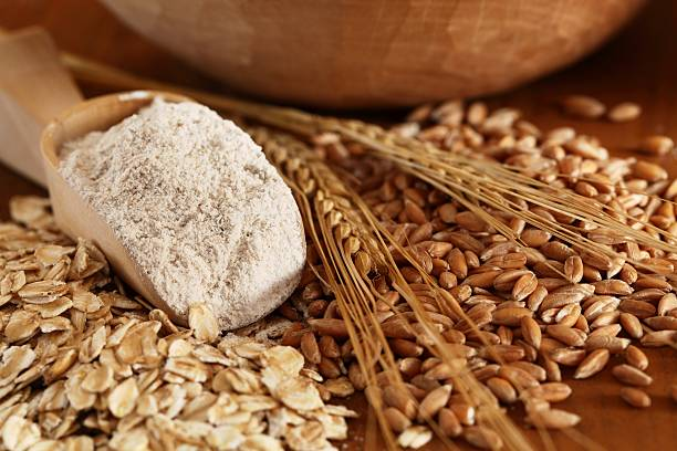 Cereal arrangement Wholegrain flour on wooden spoons, oats and corn. wholegrain stock pictures, royalty-free photos & images