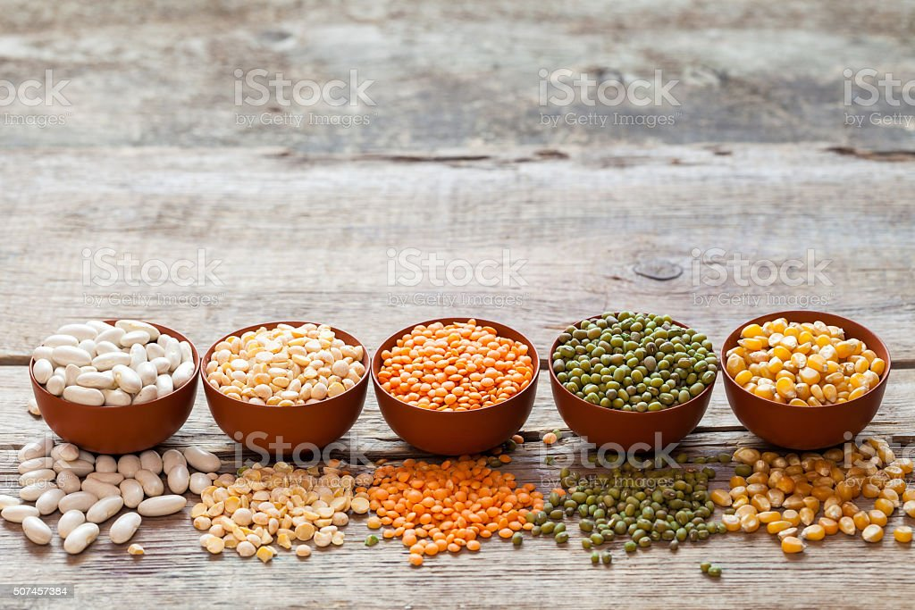 Cereal grains: red lentils, green mung, corn, bean and peas stock photo