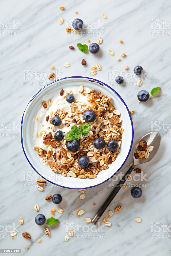 Cereals breakfast with blueberries on a marble background. Healthy morning meal with fresh berries. Top view stock photo