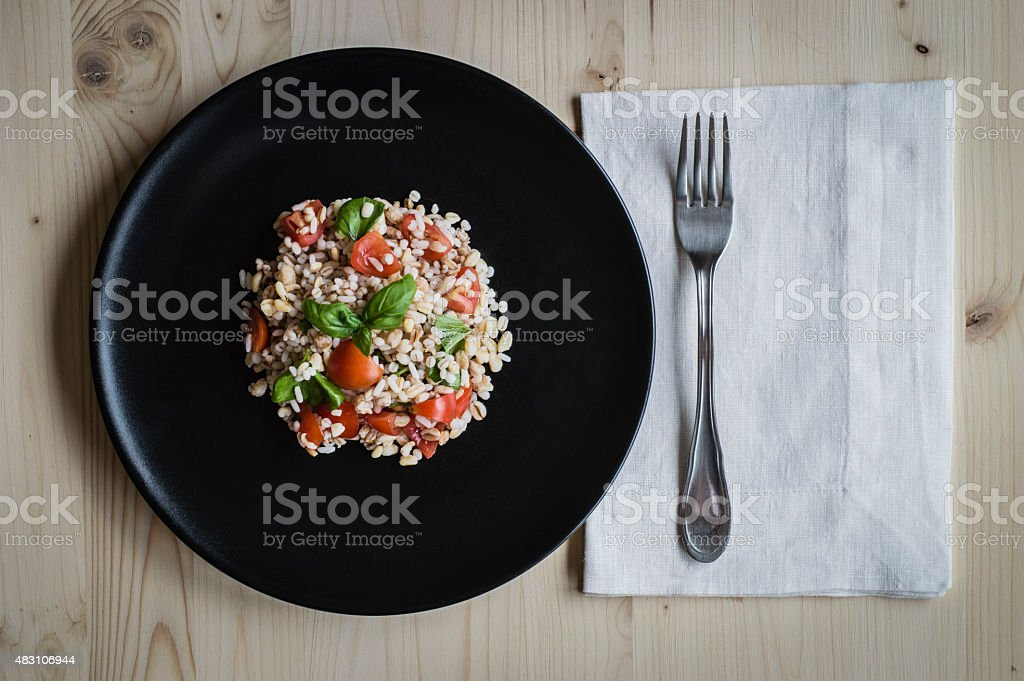 Cereals salad with tomatoes and basil in a black dish stock photo