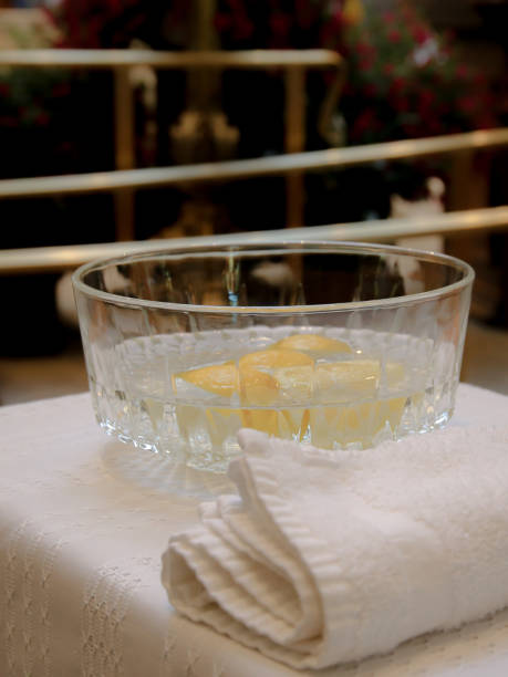 Ceremonial Church Bowl of Hand Washing Water, Lemons, White Towel on Table stock photo