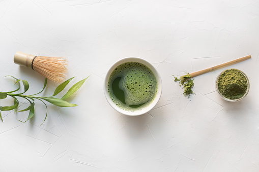 Ceremony green matcha tea and bamboo whisk on white concrete table. Top view.
