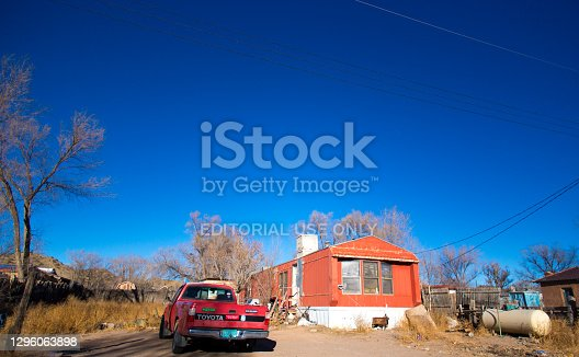 Cerrillos, NM: A red mobile home and pick-up truck in the village of Cerrillos—20 miles south of Santa Fe. Copy space available in the vibrant blue sky.