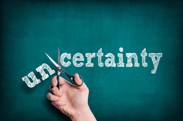 Certainty The male hand with scissors cuts word Certainty from Uncertainty. skeptic stock pictures, royalty-free photos & images