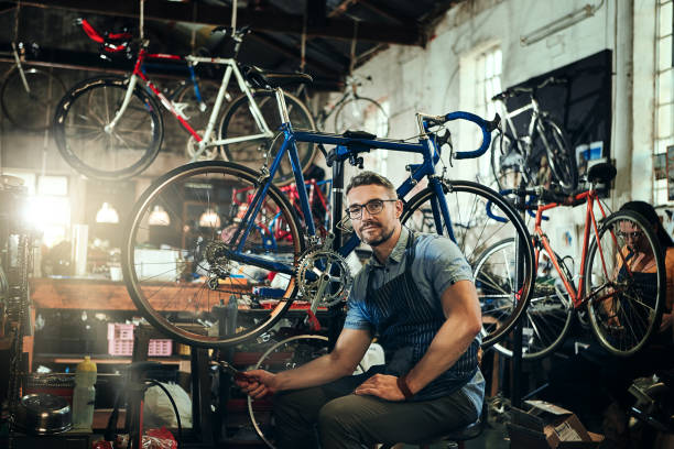 Certified to bring you top quality service Portrait of a mature man working in a bicycle repair shop with his coworker in the background bicycle shop stock pictures, royalty-free photos & images