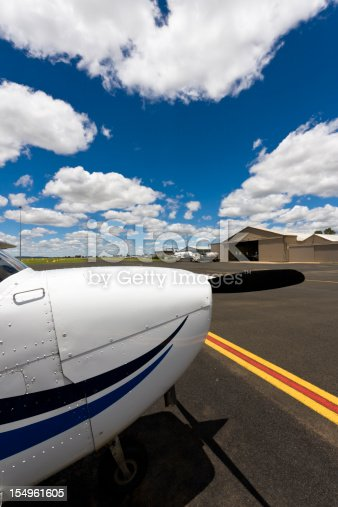 Cessna 172 with clouds and hangar in the background.