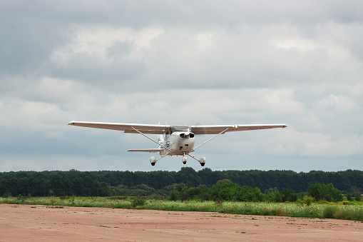 Zhitomir, Ukraine - July 31, 2011: Cessna 172S Skyhawk XP is taking off from runway into cloudy sky for a leisure flight