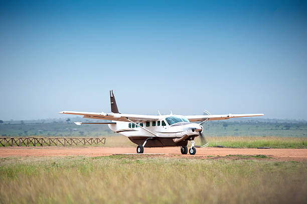 """Cessna Caravan 208 starting on an unpaved airstrip """"A Cessna Caravan 208 is starting on the unpaved runway of a bush airstrip in the Masai Mara National Park, Kenya."""" airfield stock pictures, royalty-free photos & images"""