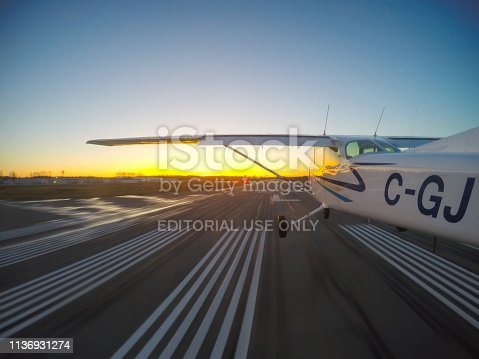 Vancouver, British Columbia, Canada - February 22, 2018: Small Airplane, Cessna 172, is landing on a runway during a vibrant sunset.