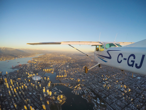 Vancouver, British Columbia, Canada - February 22, 2018: Small Airplane, Cessna 172, is flying over the city during a vibrant sunset.