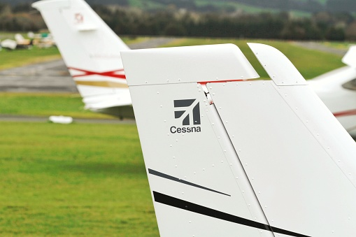 This photo is of a Cessna logo which is printed on a Cessna 172 aircraft parked at the ground at Ardmore Airport. The Cessna 172 Skyhawk is a four-seat, single-engine, high wing, fixed-wing aircraft made by the Cessna Aircraft Company.