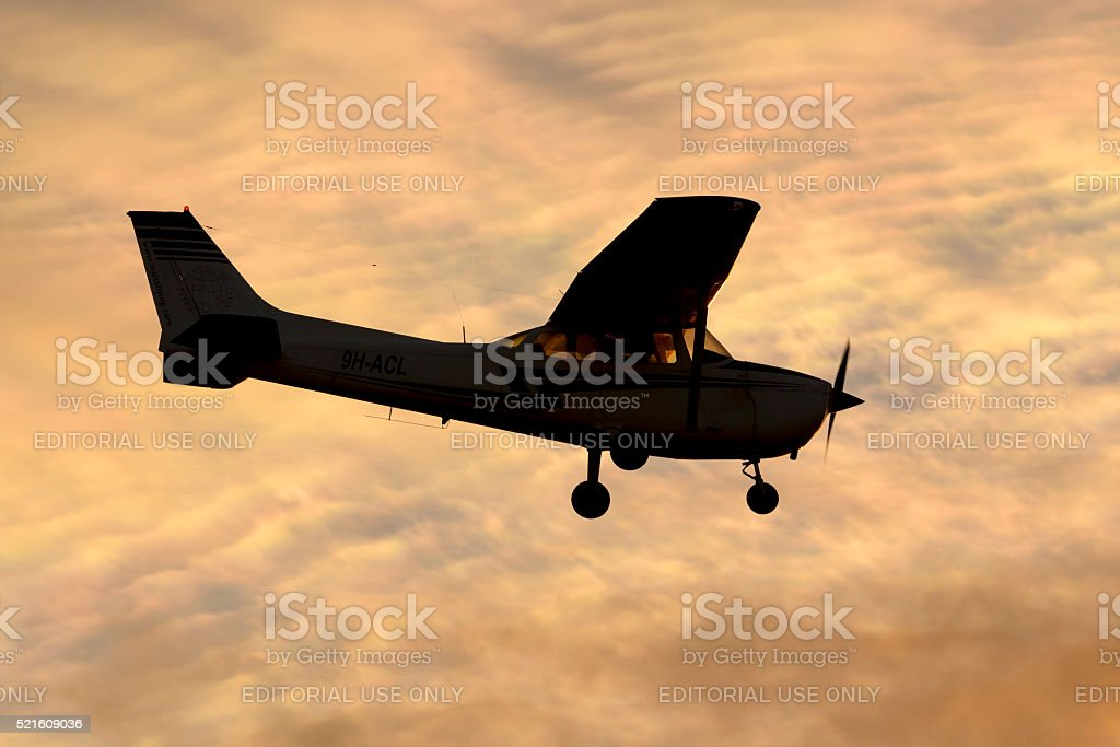 Cessna Skyhawk against clouds on sunset stock photo