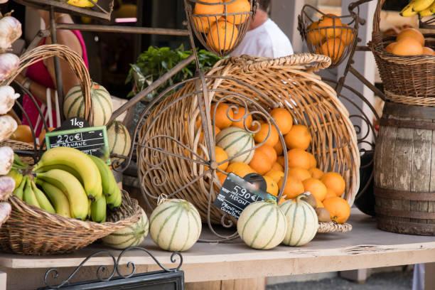 Cesto di arance e meloni in una bancarella del mercato di Moustiers Sainte-Marie in Provenza, Francia Cesto di arance e meloni in una bancarella del mercato di Moustiers Sainte-Marie in Provenza, Francia mercato stock pictures, royalty-free photos & images