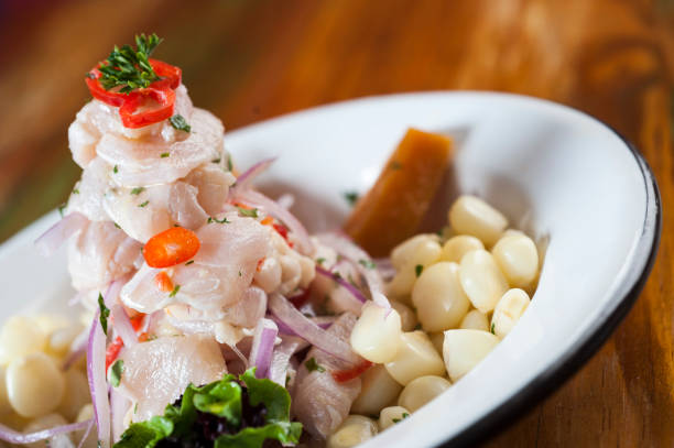 Ceviche, dish symbol of Peruvian gastronomy. Ceviche, dish symbol of Peruvian gastronomy. On a wooden table. peruvian culture stock pictures, royalty-free photos & images