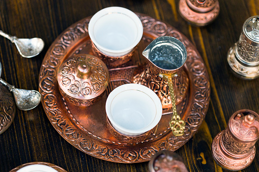 Cezve copper set for making Turkish coffee on wooden background