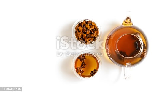 Chaga tea and chaga mushroom pieces in glass bowls and teapot isolated on a white background. Copy space, view from above.