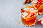 Chai spiced Apple cider cocktail for Halloween or Thanksgiving in glass on gray stone background