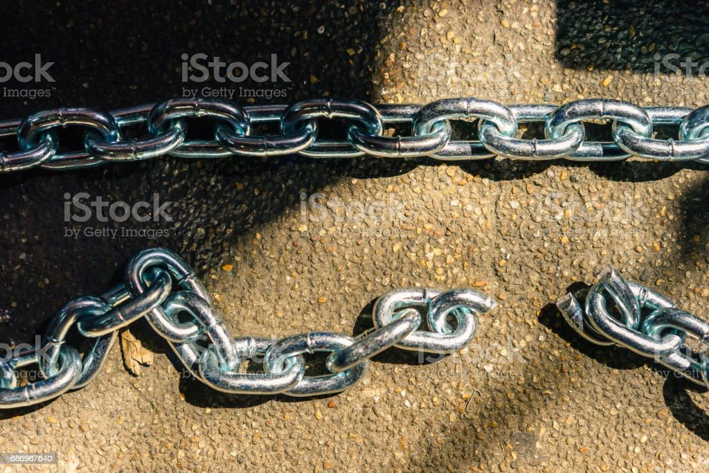 Chain and breaking chain on concrete floor background with light and shadow, vintage concepts. stock photo